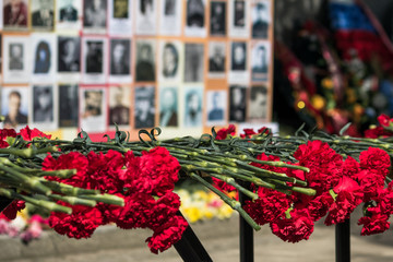 Red carnations on the background of the Immortal Regiment - the symbol of the great Victory/Victory Day
