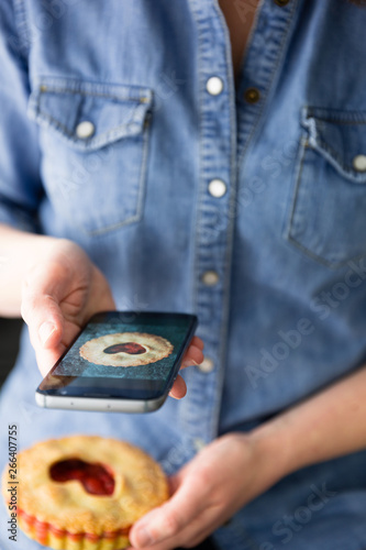 Woman taking photo on mobile of heart topped strawberry tart