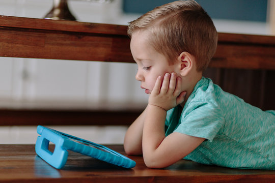 Cute young boy laying on a dining room bench watching a television show on a tablet