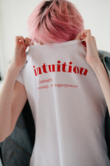 Woman hide her face behind t-shirt