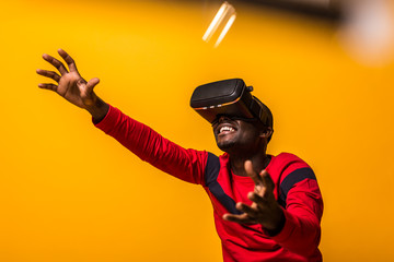 Black happy man using VR glasses over a yellow background