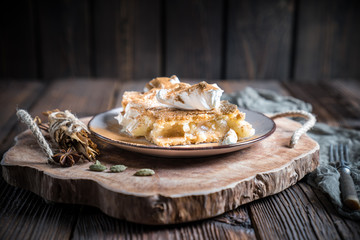Home made apple pie with cream and cinnamon on rustic wooden plate and table.