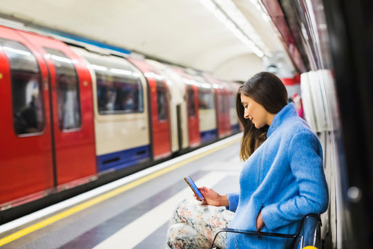 Woman using a Mobile phone while waiting for the train
