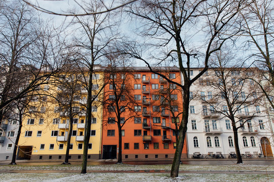 Yellow, red, and white apartment buildings in Germany with bare trees in front