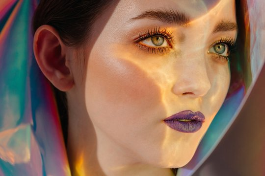 Close up of woman with purple lipstick and sunlight on face