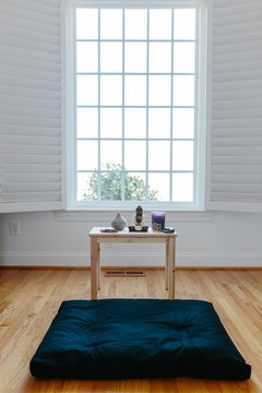 View of a meditation cushion and shrine in front of a window