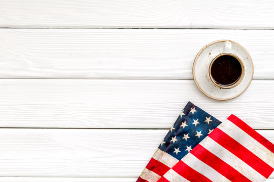 USA national day background with flag and cup of coffee on white wooden desk top view copy space