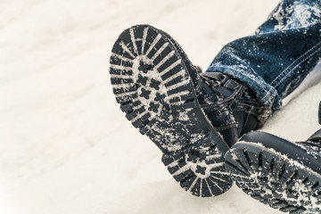 Winter boots on the feet of a boy lying in the snow
