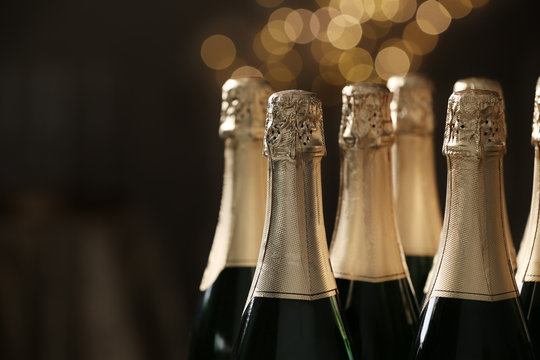 Many bottles of champagne on blurred background, closeup. Space for text