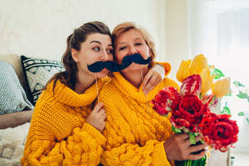 Senior mother and her adult daughter taking selfie with flowers using photo booth props at home. Mother's day concept.