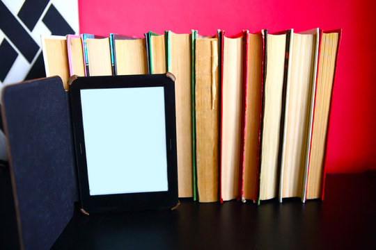 E-book in front of old paper books. Past and future concept