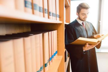 Rechtsanwalt mit Robe will zu Gericht, liest lieber noch einmal nach