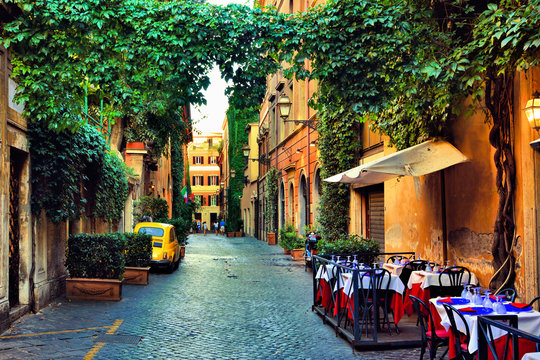 Beautiful ancient street in Rome lined with leafy vines and cafe tables, Italy