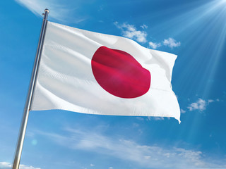 Japan National Flag Waving on pole against sunny blue sky background. High Definition