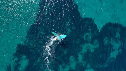 Aerial top view photo of fit man practising wind surfing in Mediterranean bay with crystal clear emerald sea