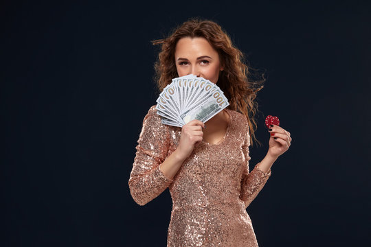 Image of lucky happy woman with brown long hair with fan of 100 dollar bills, lots of cash money, over black background