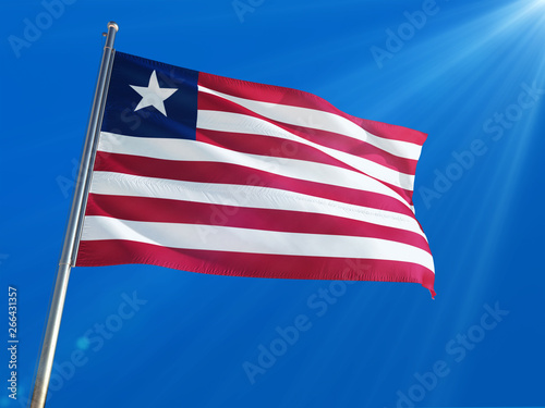 Liberia National Flag Waving on pole against sunny blue sky