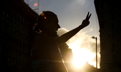 A woman dressed as former Argentina's First Lady Eva Peron, makes the victory sign during a demonstration ahead of the 100th anniversary of Evita's birth, at the Buenos Aires Obelisk