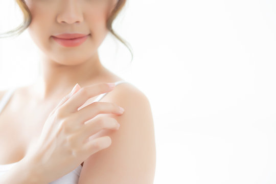 Beautiful young asian woman apply cream and treatment for skin care touch on shoulder, asia girl with lotion spa and moisturizing for health and wellness body part, lifestyle beauty cosmetic concept.