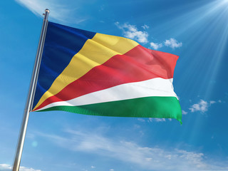 Seychelles National Flag Waving on pole against sunny blue sky background. High Definition
