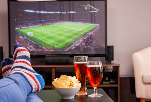 Relaxed man lying on sofa while watching football match on television, beer and chips on table