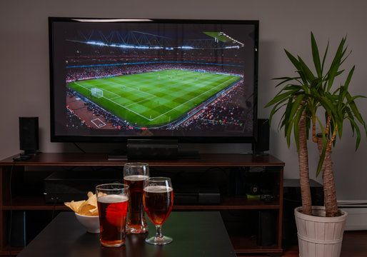 Beer glasses and chips in front of tv, football at home