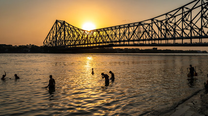 Silhouette of Howrah Bridge at the time of Sunrise.  People bathing and making rituals in the River Ganges. Papier Peint