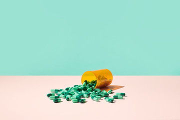 Colorful Prescription Pills Spilling Out of RX Medicine Bottle on Pale Pink Surface  with blue green background.