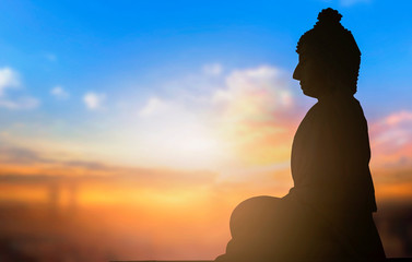 Day of Vesak concept: a statue of Buddha at sunset background
