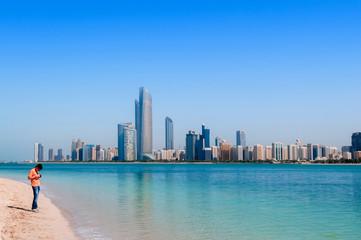 Canvas Prints Abu Dhabi Tourists on beach at marina island with modern Abu Dhabi skyline cityscape