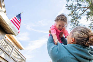 A mother holding her daughter up in the air with a United States American Flag and blue sky in the background.