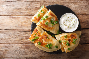 Bolani flat-bread from Afghanistan, baked or fried with a vegetable filling and served with plain yogurt closeup. Horizontal top view