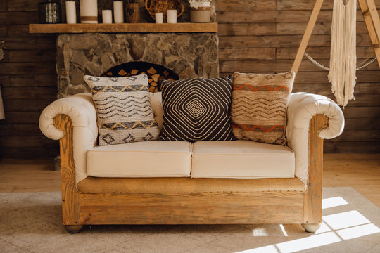 Wooden Sofa in Chalet Cozy Interior with Fireplace. Rustic Home Design for Warm Indoor Space for Alpine Vacation. Rural Cottage Living Room Decor Furniture. Winter Christmas Holiday Background