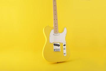 黄色背景の中の黄色いエレキギターのテレキャスター