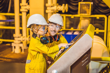 A young man and a little boy are both in a yellow work uniform, glasses, and helmet in an industrial environment, oil Platform or liquefied gas plant looking at a screen
