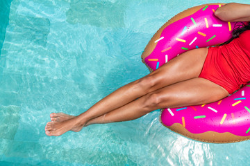 Summer vacation swimming pool woman relaxing floating on donut float in hotel holiday resort. Top view of suntan legs and swimsuit girl sunbathing.
