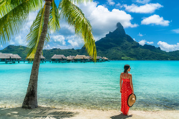 Wall Mural - Bora Bora luxury hotel vacation tourist woman relaxing by ocean beach with view of Mt Otemanu in Tahiti, Frenc Polynesia. High End resort with overwater bungalows villas.