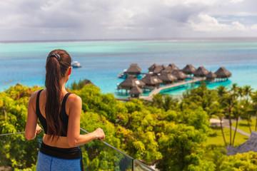Luxury Bora Bora hotel resort woman tourist overlooking view of overwater bungalows villas on Tahiti ocean, French Polynesia.