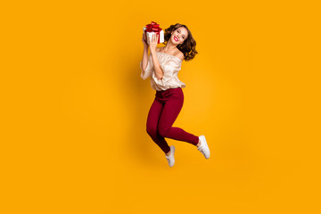 Wall Mural - Full length body size view portrait of nice attractive pretty glad cheerful cheery wavy-haired lady holding in hands box event occasion isolated over bright vivid shine yellow background