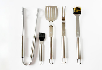 Top view object set of BBQ equipment stainless steel as tongs, carving fork, spatula in black bag . Isolated on a white background