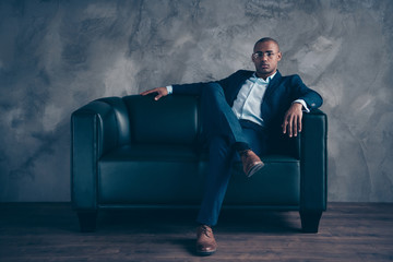 Portrait of his he nice classy chic attractive guy professional top manager ceo boss chief company director masculine sitting on couch at workplace station gray concrete wall Fototapete