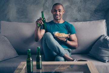 Close up photo amazing he him his dark skin macho handsome hold arms hands green bottle ale cider potato fried fast food pause break wear blue t-shirt pants sit comfy divan room office house indoors