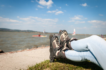 Close up picture of a woman legs wear inline roller blades near a strand of a lake