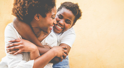Happy young mother having fun with her kid - Son hugging his mum outdoor - Family connection,...