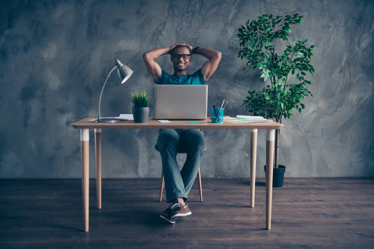 Full length body size photo amazing he him his handsome look notebook table talk speak skype hands arms behind head green plant wear specs blue t-shirt pants sit chair indoors workstation office