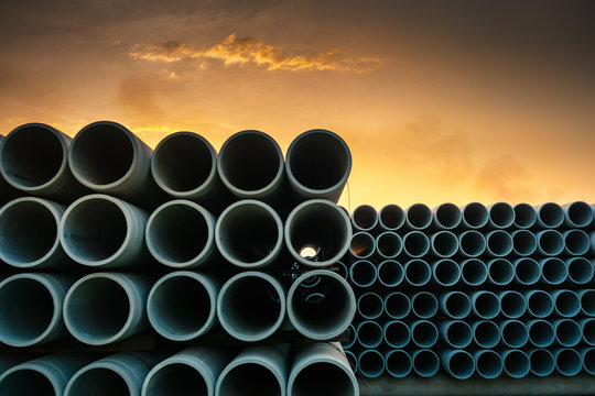 Row of Drainage Sewage Concrete Pipeline Storage, Stack of Culvert Pipe and Waste Water Treatment System of Manufacturing Plant. Cement Water Culvert Pipes for Construction