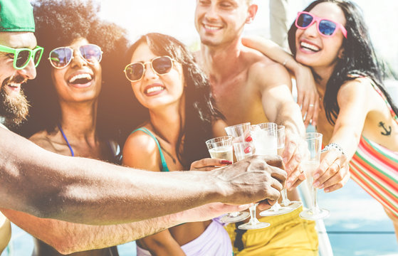 Happy friends cheering with champagne in summer boat party - Young people having fun drinking and laughing together - Youth lifestyle and vacation concept - Focus on left black hand