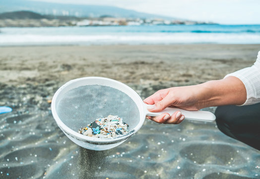 Young woman cleaning microplastics from sand on the beach - Environmental problem, pollution and ecolosystem warning concept - Focus on hand
