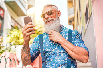 Trendy senior man using smartphone app in downtown center outdoor - Mature fashion male having fun with new trends technology - Tech and joyful elderly lifestyle concept - Focus on his face Wall mural