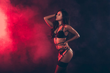 Profile side view portrait of nice lovely magnificent stunning charming attractive sportive wavy-haired lady wearing swordbelt teasing posing isolated over black red light background